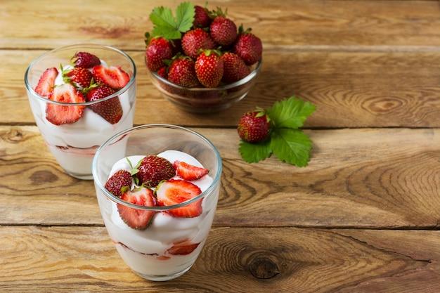 Summer layered cream dessert and ripe strawberry in glass bowl