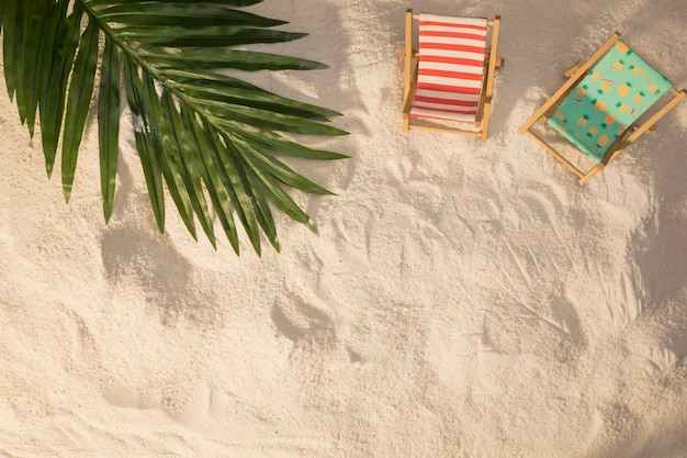 Summer layout of palm tree leaf and small deckchairs on and