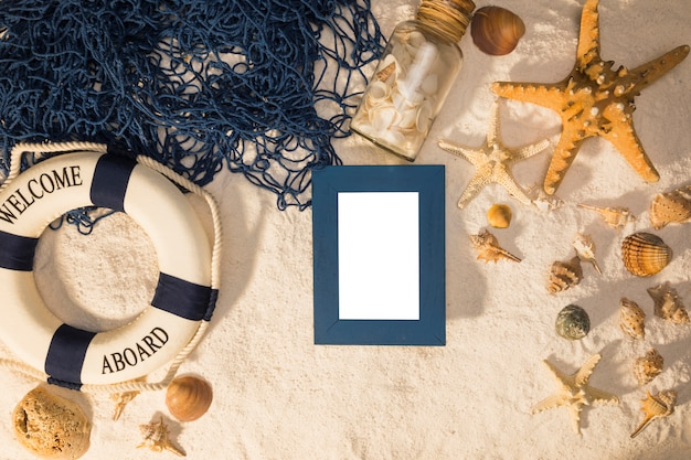 Summer layout of whiteboard starfish seashells lifebuoy and fishing net on sand