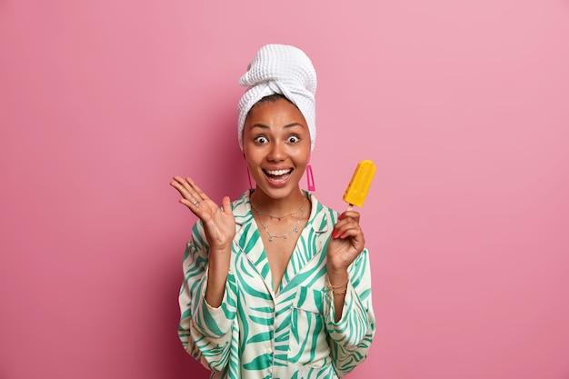 Estate, tempo libero e dessert freddo. la donna dalla pelle scura positiva sorridente tiene un delizioso gelato al mango giallo sul bastone, si sente eccitata e alza la mano, indossa un asciugamano avvolto sulla testa dopo la doccia