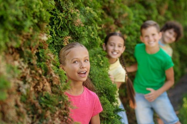 여름 레저. 여름날 야외에서 시간을 보내는 덤불 밖을 바라보며 웃고 있는 행복한 장발 소녀와 친구들