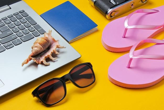 Летний отдых. летний отдых. ноутбук и пляжные аксессуары на желтом фоне. студия короткая. пляжный объект.