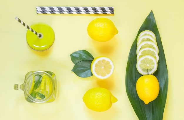 Summer lemon composition for cooking detox lemonade with mint and ice in mason jar on yellow.