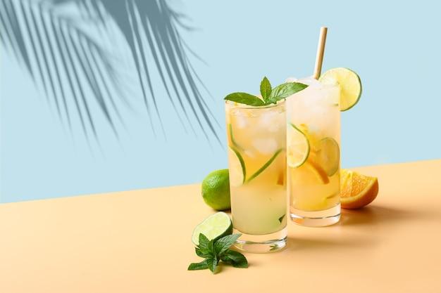 여름 레모네이드 또는 칵테일 컬러 배경 상쾌한 음료에 오렌지와 라임 슬라이스