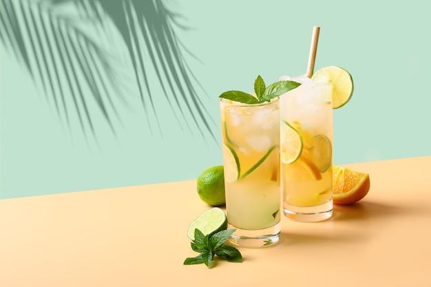 여름 레모네이드 또는 모히토 칵테일 컬러 배경에 오렌지와 라임 슬라이스