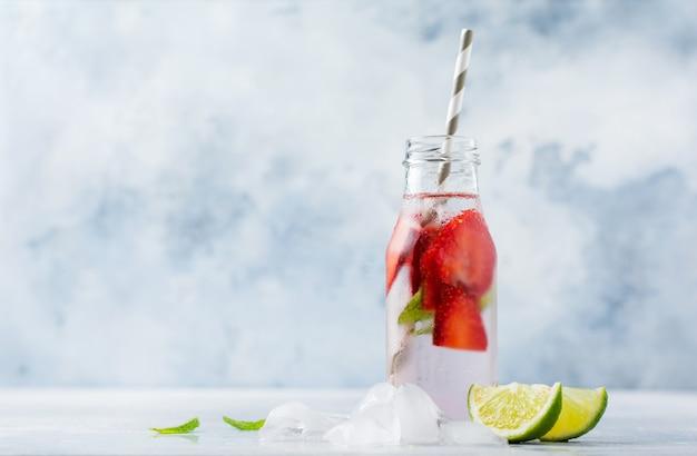 얼음, 딸기, 민트, 라임 병 및 콘크리트 회색 배경에 종이 튜브와 함께 여름 레모네이드. 건강한 음주 개념.