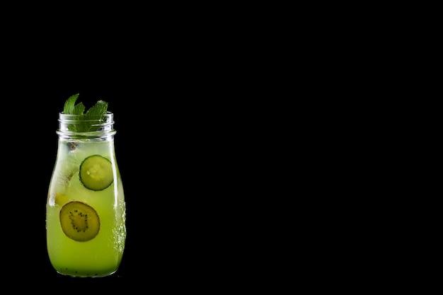 Летний лимонад с киви и огурцом, изолированных на черном.