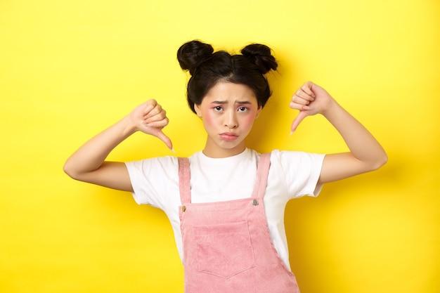 夏のライフスタイルのコンセプト。化粧、指を下に向け、しかめっ面の動揺、不公平な状況、黄色の背景に失望した悲しくて暗いアジアの女性