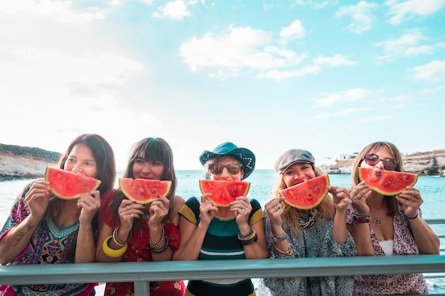 レジャーを楽しむトレンディな人々の陽気な幸せな女性のグループと夏のライフスタイルのコンセプト