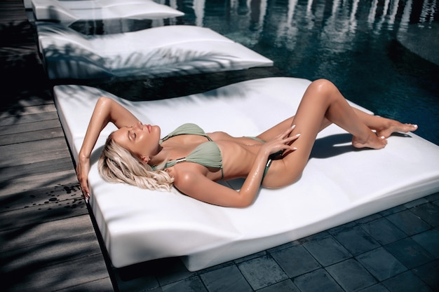 Summer lifestyle fashion portrait of young stunning tanned woman. enjoying life sunbed near the pool. wearing stylish grey bikini. sunbathing.