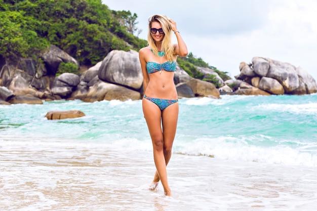 Портрет летнего образа жизни идет молодая сексуальная блондинка с подтянутым загорелым телом, в стильном бикини и солнцезащитных очках, весело на пляже острова. гулять в одиночестве и думать о ком-то. романтическое настроение.