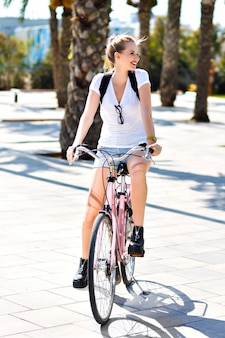 Summer lifestyle portrait of happy joyful blonde hipster girl, sportive fit days, riding vintage pink bike, travel with backpack at exotic country, having fun outdoor, palms, park, nature.