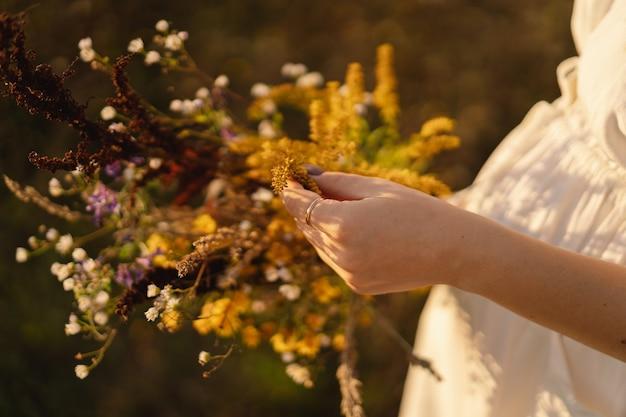 그의 머리에 야생 꽃 화 환의 화 환에 아름 다운 젊은 여자의 여름 라이프 스타일 초상화