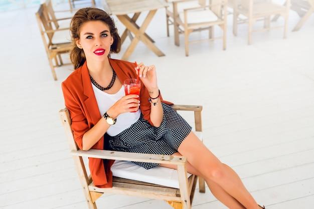 かわいいかなり若い女性が屋外でポーズ、ビーチカフェに座っているとエキゾチックなカクテル、海の背景を飲むの夏のライフスタイルの肖像画。明るい色。休暇気分。笑顔で楽しんでください。