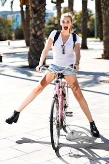 幸せなうれしそうな金髪流行に敏感な女の子、陽気なフィットの日、ビンテージピンクバイクに乗って、屋外、ヤシの木、公園、自然を楽しんで、エキゾチックな国でバックパックで旅行の夏のライフスタイルの肖像画。