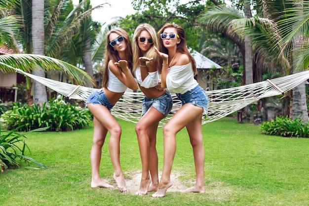 熱帯の国で素敵な夏の日に一緒に楽しんで、デニムショートパンツの白のトップスとサングラスを身に着けて空気キスを送るツリーかなり若い女性の友人の夏のライフスタイルの肖像画。