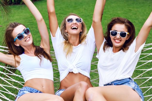 クレイジーになって、叫んで、一緒に楽しんで笑って、ハンモックでジャンプして、木の女性の夏のライフスタイルの肖像画。白のトップスとサングラスを身に着けて、パーティー、喜び、楽しみの準備ができています。