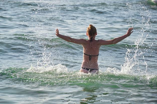 Summer lifestyle portrait of pretty young girl having fun on a tropical beach, splashing sea water