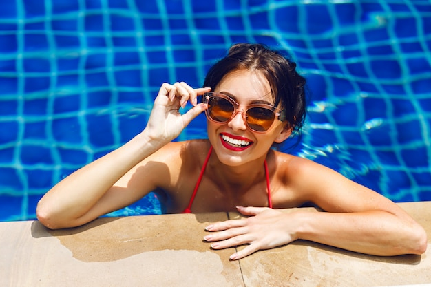 Summer lifestyle portrait of sexy stunning beauty woman swimming on pool, getting sunbathing and relax, luxury vacation.