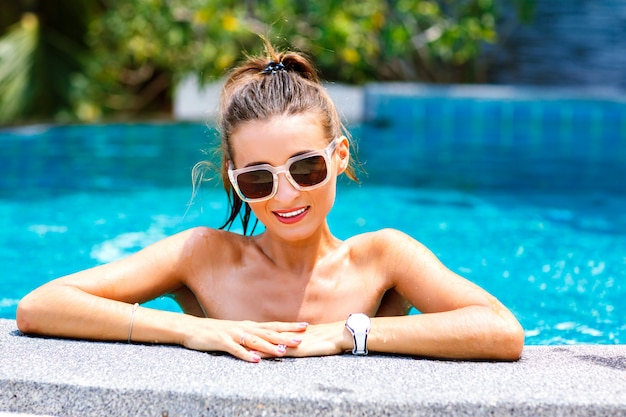 Summer lifestyle portrait of sexy woman posing near pool, bright sunny colors. wearing stylish bikini and sunglasses.