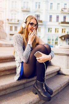 Summer lifestyle sunny image of pretty young blonde woman listening to music by earphones , holding mobile phone, sitting on the street, dreaming. wearing stylish spring outfit.