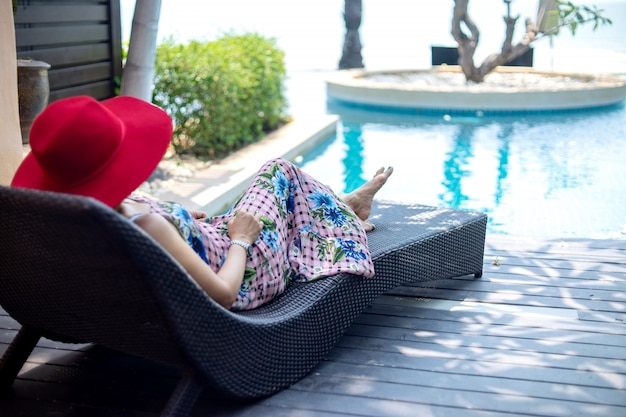 Summer lifestyle woman with red hat lay on sunbed near swimming pool.