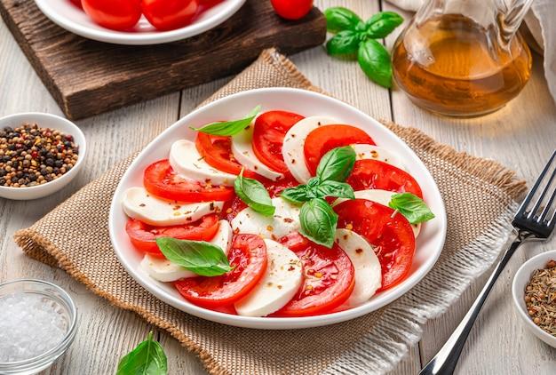 Летний легкий итальянский салат капрезе с помидорами, сыром моцарелла, базиликом и оливковым маслом. боковой вид крупным планом.