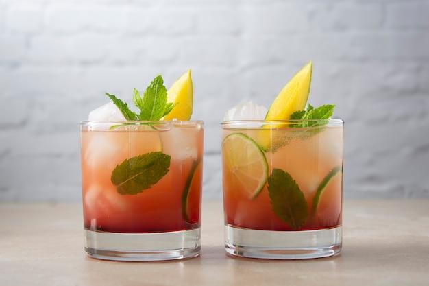 Летний освежающий коктейль из манго, приготовленный из свежего сока манго, кубиков льда и листьев мяты. розовый коктейль с фруктами