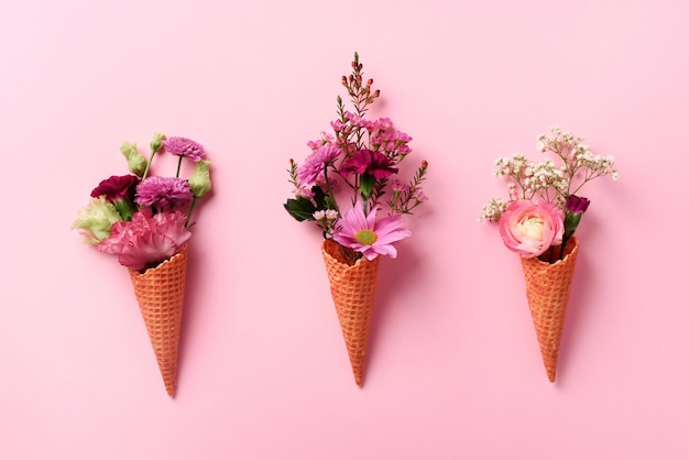 Summer minimal concept. ice cream cone with pink flowers and leaves on punchy pastel background.