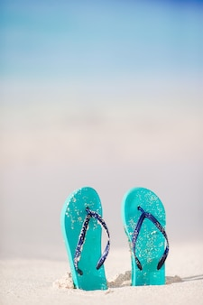 Summer mint flip flops with sunglasses on white beach