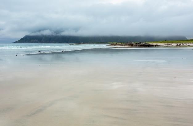 ランバーグ(ノルウェー、ロフォーテン諸島)の白い砂浜と空の反射を伴う夏の霧と曇りのビーチビュー。
