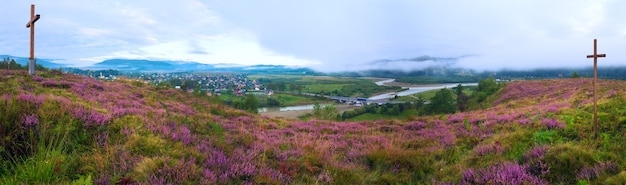 Summer misty morning country foothills panorama with heather flowers and wooden cross (lviv oblast, ukraine) . three shots stitch image.