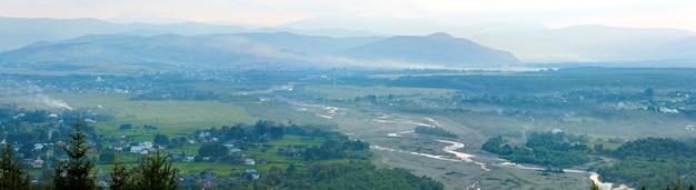 夏の霧のかかった朝の山村のパノラマ(田園風景)。 3ショットステッチ画像。 Premium写真