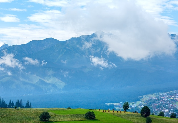 Summer misty mountain village outskirts with tatra range  (gliczarow gorny, poland)