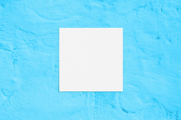 Summer modern sunlight stationery  scene. flat lay top view blank greeting card on grunge concrete turquoise background.