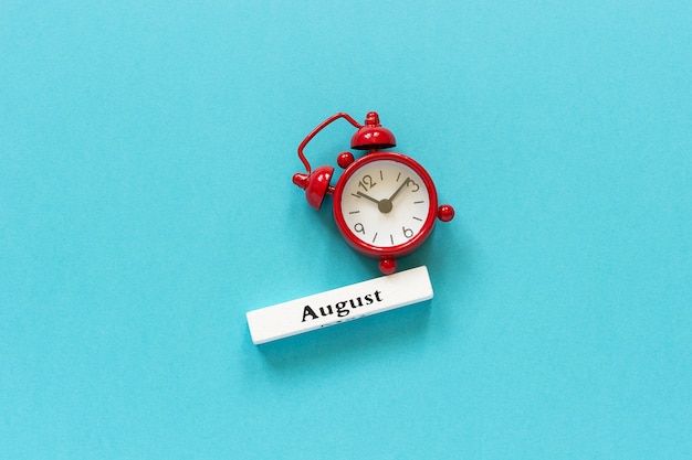 Summer month august and red alarm clock on blue paper. concept hello august