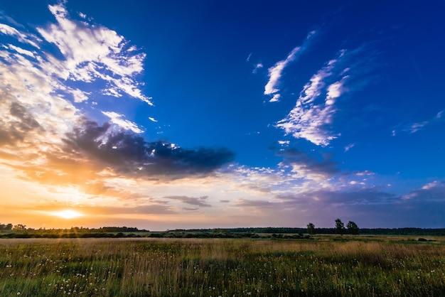 Летний утренний пейзаж с красочным восходом солнца и солнечными лучами в небе с облаками над лугом