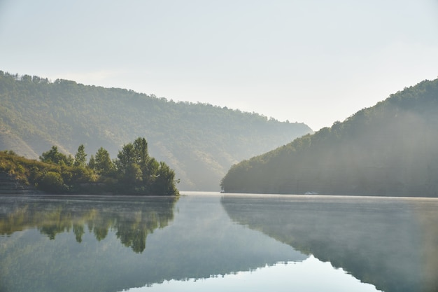 Summer morning in mountains by river.