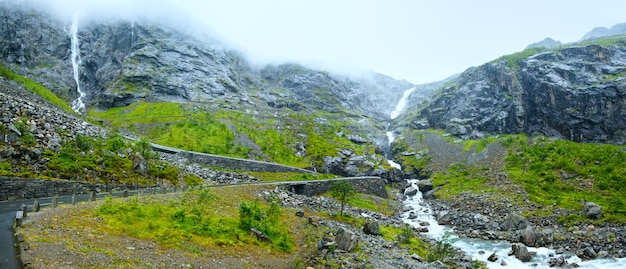 Summer mountain cloudy view with waterfall on trollstigen (the troll steps) slope (norway).