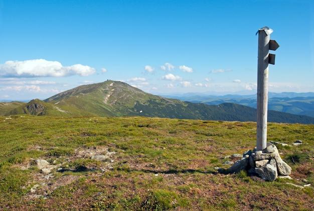 Летний горный пейзаж со знаком направления