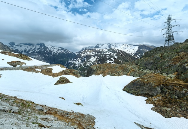 Summer mountain landscape with road and electric pole (grimsel pass, switzerland)