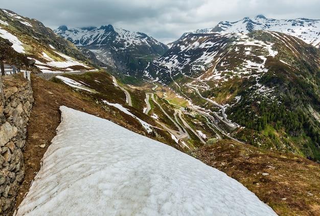 曲がりくねった高山道路のある夏の山の風景(グリムゼル峠、スイス)