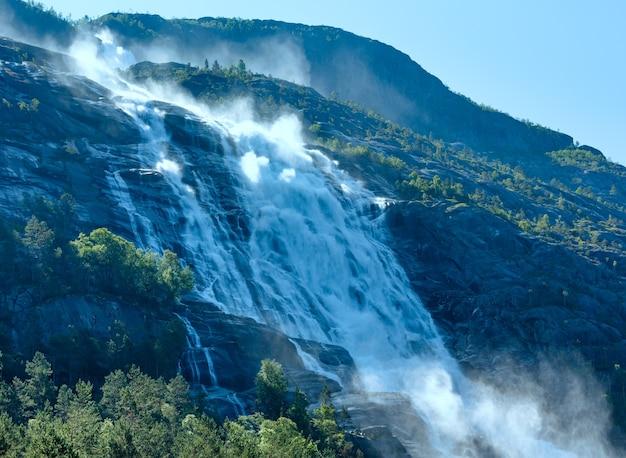 Summer mountain  langfossen waterfall on slope (etne, norway).