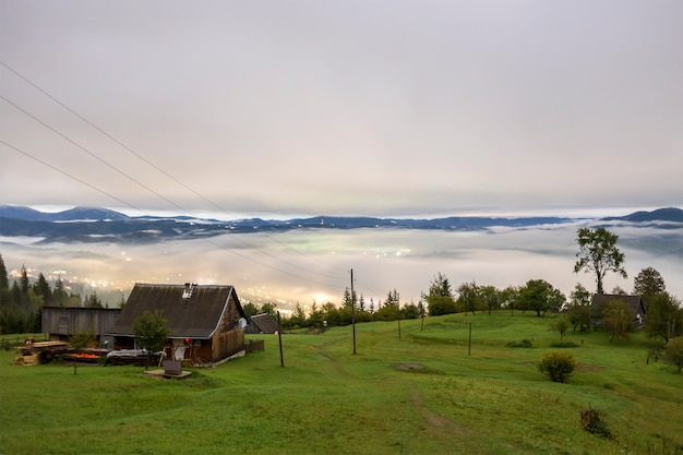 Summer mountain panorama. small wooden house cottage and barn on green mountain valley on bright foggy sky, clouds and mountain ridge copy space background.