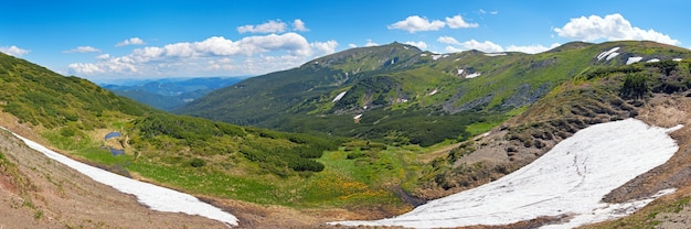 Summer mountain view with snow on mountainside (with observatory ruins on chornogora ridge, ukraine). seven shots stitch image.