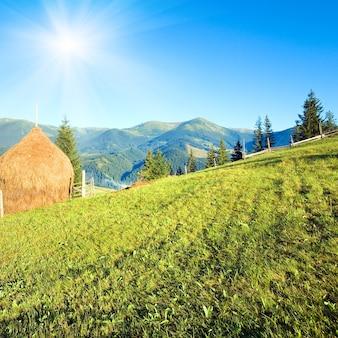 干し草の山と太陽の光が降り注ぐ夏の山間の村