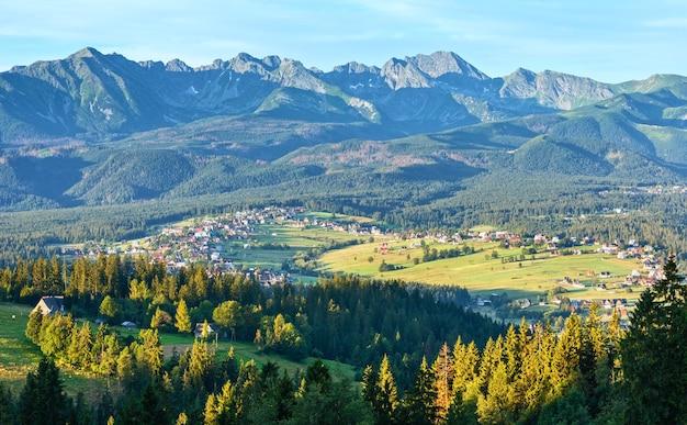 夏の山間の村の郊外と谷のグリツァルフドルニーの後ろのタトラ山脈