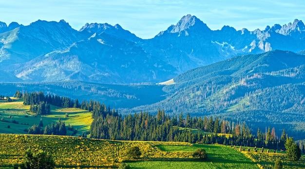 Summer mountain village outskirts and tatra range behind (gliczarow gorny, poland)