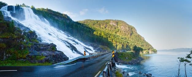 Summer mountain waterfall on slope near road along the sandvinvatnet lake (norway). panorama.