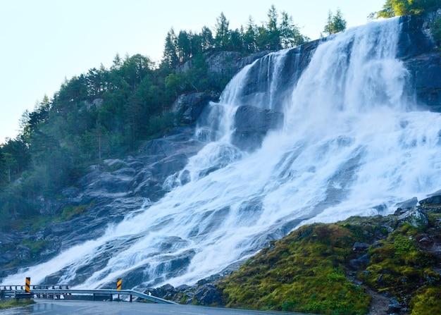 Summer mountain waterfall on slope near road along the sandvinvatnet lake (norway).